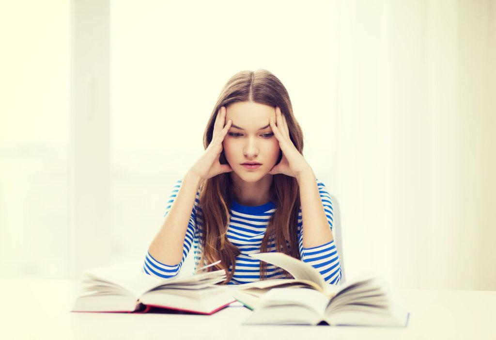 education and home concept - stressed student girl with books